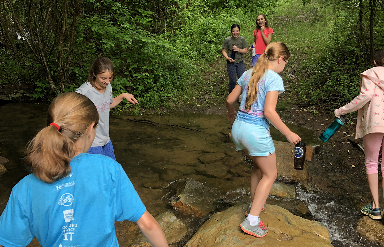 Village School students crossing a stream during the Wildrock Field Trip - 2018
